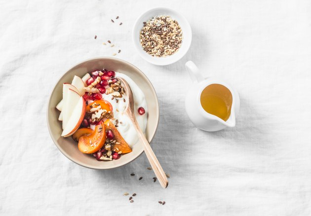 Full fruit and greek yogurt breakfast bowl. Persimmon, apple, walnuts, pomegranates and natural yogurt. Healthy food concept on light background, top view