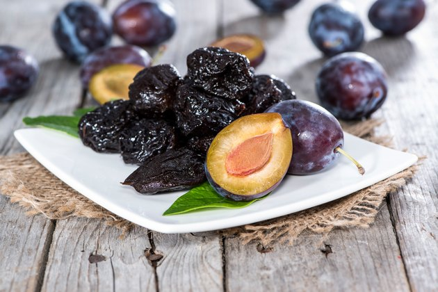 Fresh plums and prunes on a plate