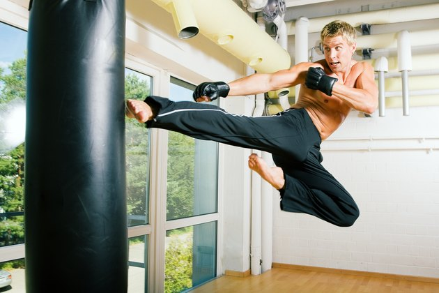 A topless man jumping up and kicking a heavy kicking bag