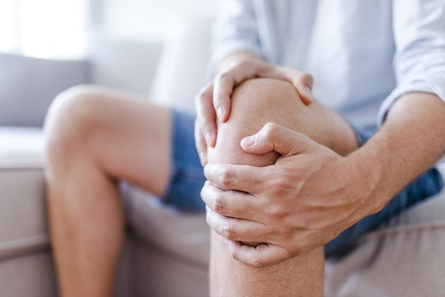 An older man sitting on the couch and massaging joint pain in his knee