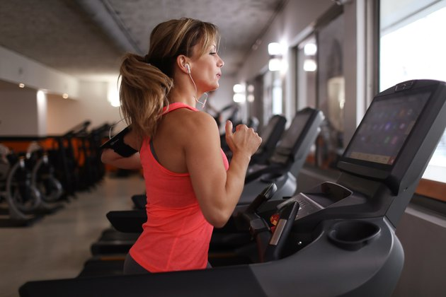 Woman running on treadmill at fitness center