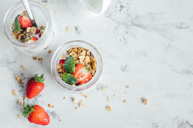 Two jars with tasty parfaits made of granola, strawberries and yogurt on white marble table. Top view, copy space