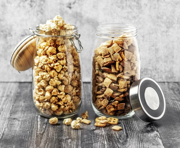 Two jars with caramelized popcorn and snack mix on gray background