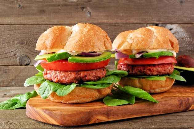 Plant based meatless burgers with avocado, tomato and spinach against a wood background