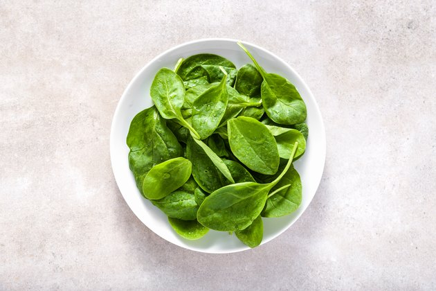Fresh spinach. Green vegetable leaves on plate, healthy food, vegetarian diet concept.
