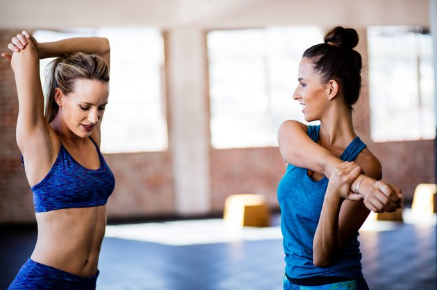 Girls stretching sholder muscles after a gym workout at gym