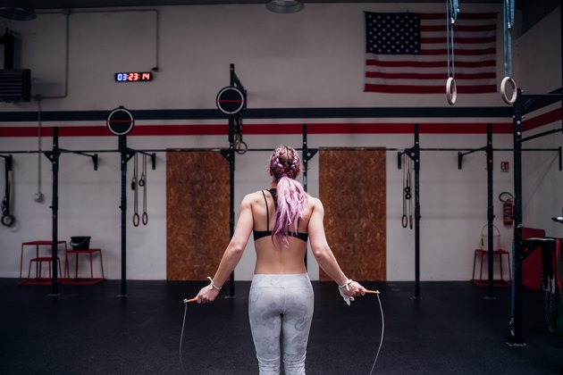 Young woman training, holding skipping rope in gym, rear view
