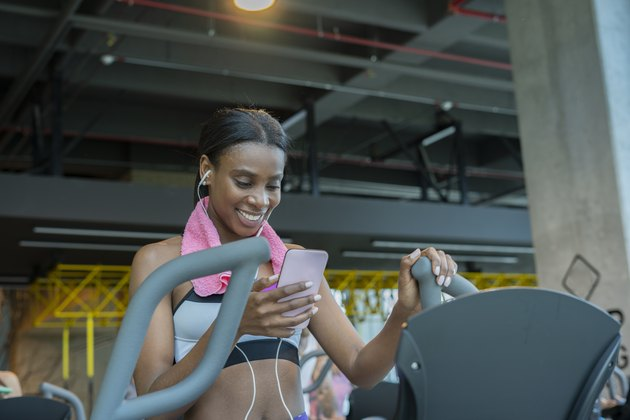 young latin woman trains in the gym elliptical while listening to music through her headphones