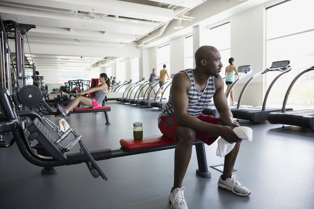 Pensive man resting on bench at gym during mindful workout