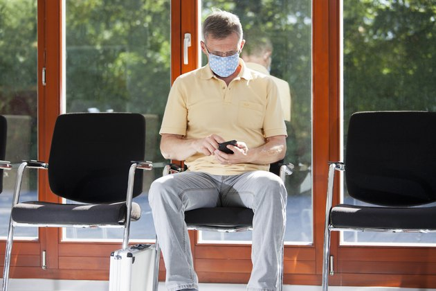Mature man with face mask sitting in a bright waiting room of a hospital or an office looking at corona app of his smart phone