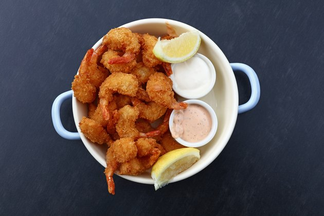 Portion of breaded shrimps with dipping sauces
