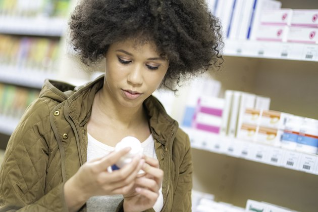 A young woman looking at supplements in a pharmacy