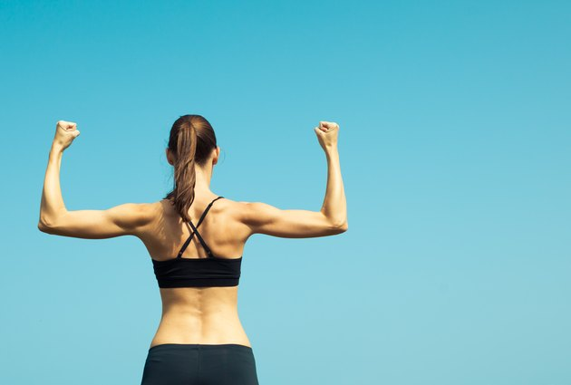 Portrait of strong female flexing