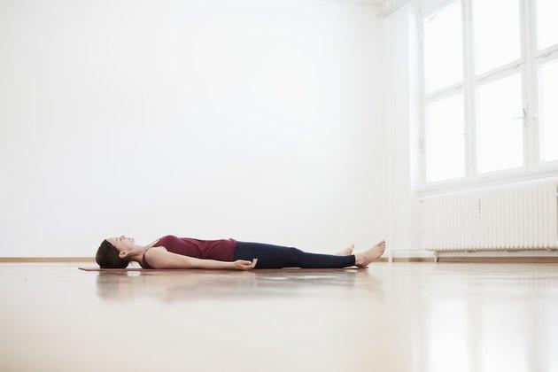Woman in exercise studio lying on back on floor