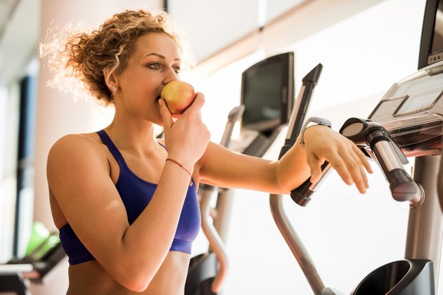 Athletic woman eating preworkout meal apple and in a gym.