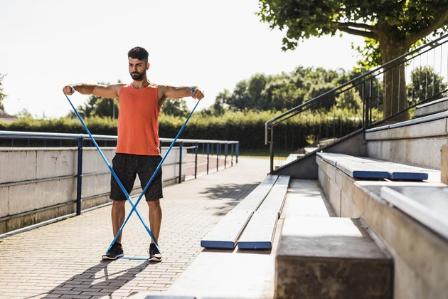 man exercising with resistance band outside