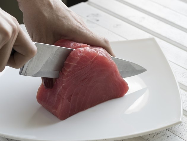 Yellow Fin Tuna being cut up for cooking. Tuna Fish.