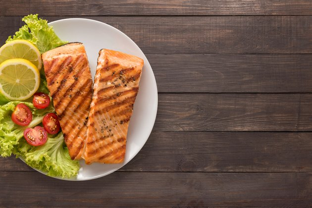Grilled salmon with lemon, tomato on the wooden background.