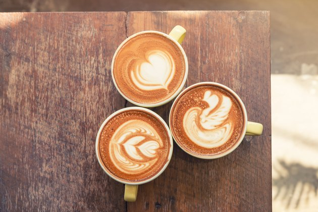 Top view of three cups of coffee in yellow cups with various types of latte art
