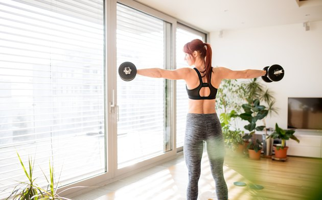 Young fitness woman doing exercise with dumbbells at home.