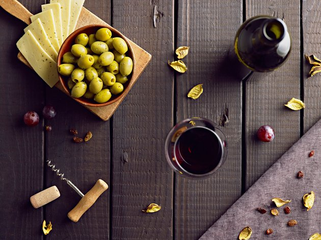 Red vine served with green olives and cheese.