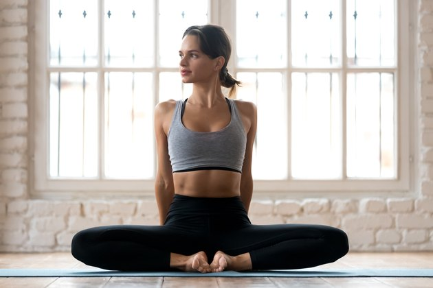 Young sporty attractive woman practicing yoga, doing Butterfly exercise