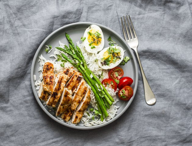Healthy lunch - rice, asparagus, grilled chicken, boiled egg on a grey background, top view