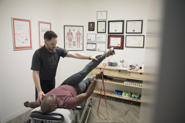 Male physiotherapist helping client stretching with resistance band in office
