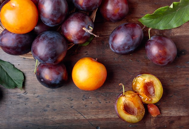 Ripe juicy plums on a old wooden table.