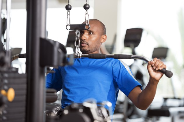 Man in a blue shirt using the lat pulldown machine at the gym