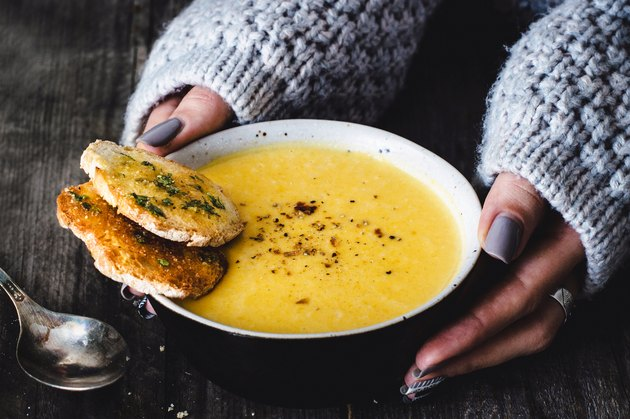 A woman on the soup diet eating carrot pumpkin cream soup with garlic bread