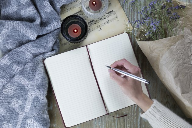 woman's hand writing in notebook near candles and flowers