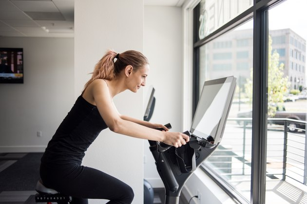 Woman working out on exercise bike in workout room