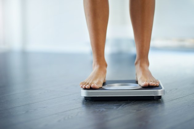 View of a woman's bare feet on a black bathroom scale