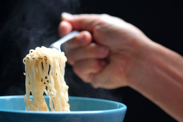Hand holding fork full of hot noodles from soup in a blue bowl.