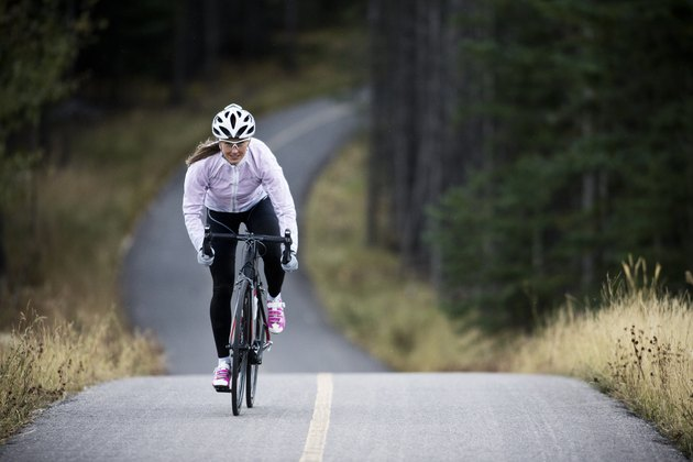 A woman rides her road bike along the Trans Canada Trail bikepath near Canmore, Alberta, Canada in the autumn.