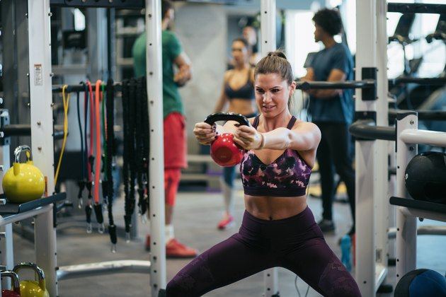 Young woman doing kettlebell exercise at gym
