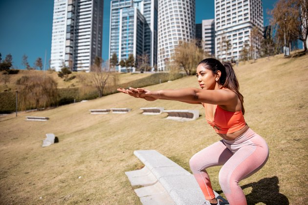 Young woman doing a leg toning workout in the morning in a public park