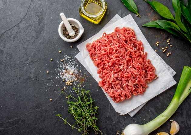 Mince. Ground meat with ingredients for cooking on black background. Minced beef meat. Top view