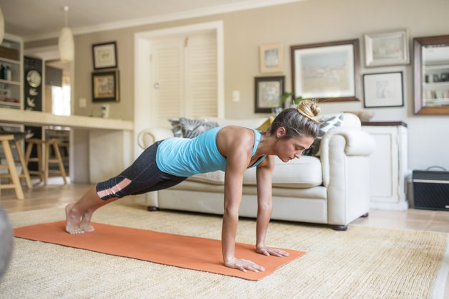 Woman practicing in plank pose on mat at home