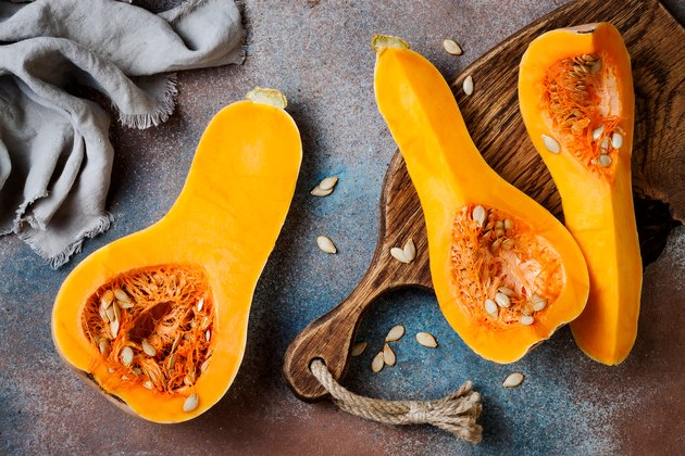 Butternut squash on wooden board over rustic background. Healthy fall cooking concept