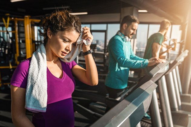 Young tired woman wiping sweat with towel while running on a treadmill in a gym