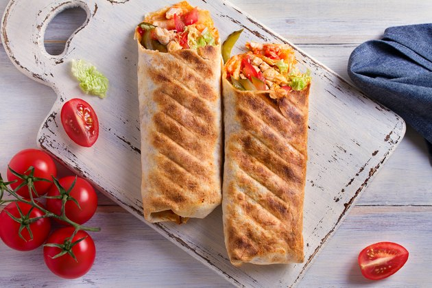 Chicken wraps with tomatoes, pickles, cabbage and onion. Tortilla, burritos, sandwiches, twisted rolls
