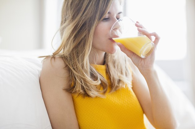 Woman drinking orange juice, sugary foods
