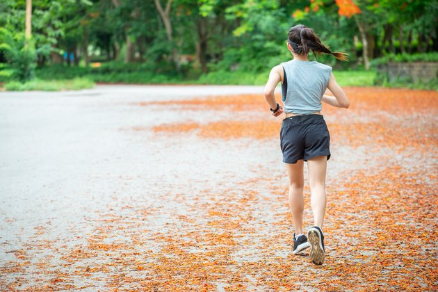 Back view of young runner woman running in the park.
