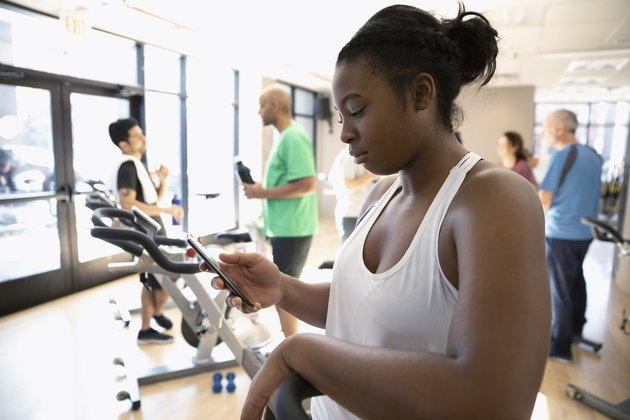 Woman using smart phone after exercise class in gym