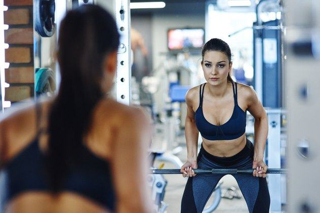 Woman lifting barbell in gym looking in mirror