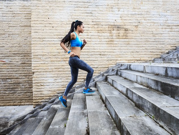 Female runner moving up on stone stairs-side view