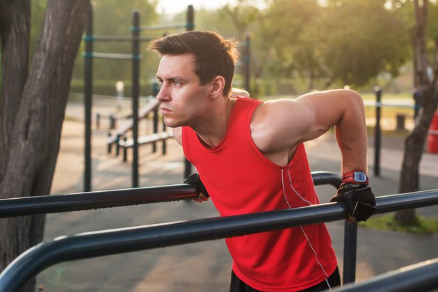 Fit man workout out arms on dips horizontal bars training