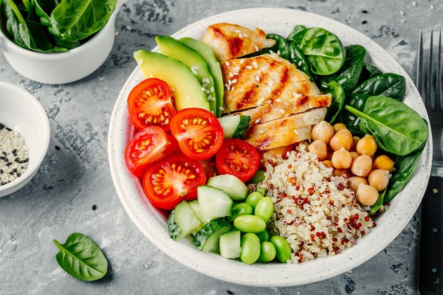 Buddha bowl with spinach salad, quinoa, chickpeas, grilled chicken, avocado, tomatoes, cucumbers, sesame seeds.